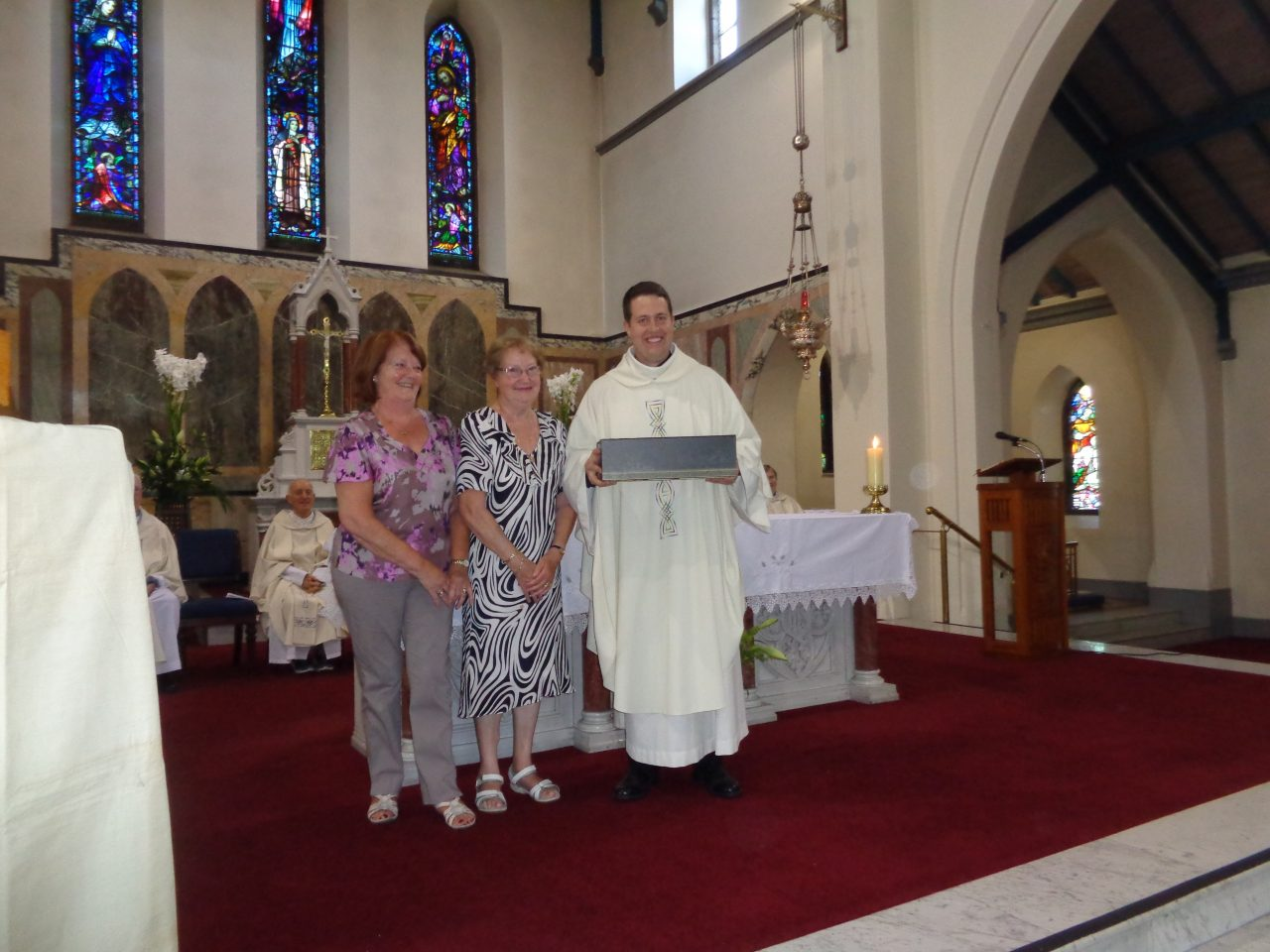 Lily Curtis and Breda Whelan present Fr. Tom with a Gift from the Parish