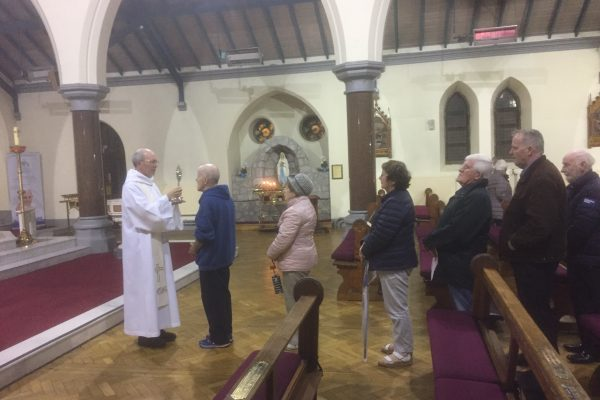 Fr. David blesses Parishioners with the Relic of St. Teresa